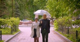 Close-upspruit van jong mooi hipsterpaar die een paraplu houden samen lopend naar camera die gelukkig in zijn stock footage