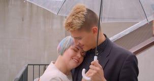 Close-upspruit van jong mooi hipsterpaar die elkaar bekijken die zich onder paraplu verenigen die gelukkig zijn stock video