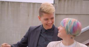 Close-upspruit van jong mooi hipsterpaar die en camera draaien bekijken die samen bevinden gelukkig zijnd zich in openlucht binne stock footage