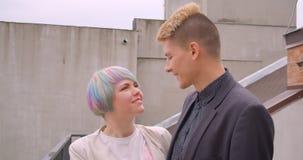Close-upspruit van jong mooi hipsterpaar die samen bevinden gelukkig zijnd zich in openlucht in de stedelijke stad stock videobeelden