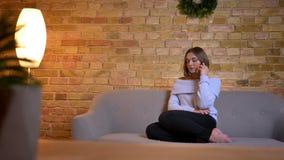 Close-upspruit van jong mooi Kaukasisch wijfje die op de telefoon spreken emotioneel terwijl het zitten op de bank bij comfortabe stock videobeelden