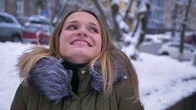 Close-upspruit van jong mooi Kaukasisch wijfje met donkerbruin en haar die dreamful op de sneeuwstraat in a glimlachen zijn stock footage