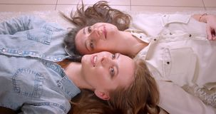 Close-upspruit van jong mooi lesbisch en paar die gelukkig leggend op de vloer in onlangs gekocht glimlachen lachen stock video