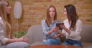 Close-upspruit van jong mooi lesbisch paar die aan vrouwelijke makelaar in onroerend goed met de tablet over aankoop van een flat stock video