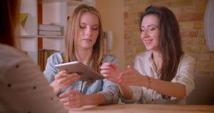 Close-upspruit van jong mooi lesbisch paar die aan vrouwelijke makelaar in onroerend goed met de tablet over aankoop van een flat stock footage