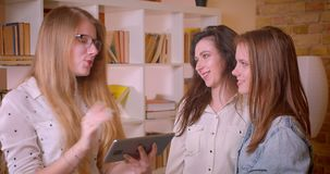 Close-upspruit van jong mooi lesbisch paar die aan vrouwelijke makelaar in onroerend goed met tablet over het kopen van een flat  stock footage