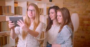 Close-upspruit van jong mooi lesbisch paar die aan vrouwelijke makelaar in onroerend goed met touchpad over het kopen van een fla stock footage