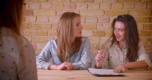 Close-upspruit van jong mooi lesbisch paar die aan vrouwelijke makelaar in onroerend goed over aankoop van een flat spreken die a stock video