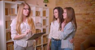 Close-upspruit van jong mooi lesbisch paar die aan vrouwelijke makelaar in onroerend goed over aankoop van een flat spreken stock video
