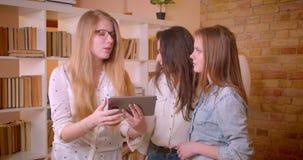 Close-upspruit van jong mooi lesbisch paar die aan vrouwelijke makelaar in onroerend goed over het kopen van een flat spreken stock videobeelden
