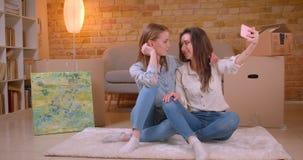 Close-upspruit van jong mooi lesbisch paar die bij camera stromen spreken levend op telefoon het koesteren gelukkig en stock video