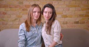 Close-upspruit van jong mooi lesbisch paar die camerazitting bekijken op de laag in een onlangs gekochte flat stock footage