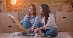 Close-upspruit van jong mooi lesbisch paar die cheerfully de plaatsing van de beeldzitting bespreken op de vloer stock video