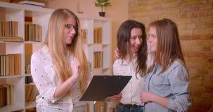 Close-upspruit van jong mooi lesbisch paar die een bespreking met vrouwelijke makelaar in onroerend goed over aankoop van een fla stock footage
