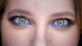 Close-upspruit van jong mooi vrouwelijk gezicht met ogen die camera met gekke gelaatsuitdrukking met mooi bekijken stock video