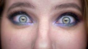 Close-upspruit van jong mooi vrouwelijk gezicht met ogen die camera met gelukkige gelaatsuitdrukking met mooi bekijken stock footage