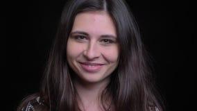 Close-upspruit van jong schitterend Kaukasisch wijfje die gelukkig en camera met achtergrond bekijken glimlachen die op zwarte wo stock videobeelden