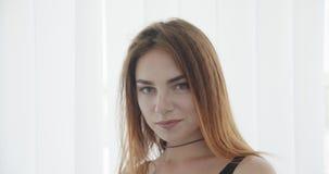 Close-upspruit van jong sexy Kaukasisch wijfje in zwarte bodysuit die camera bekijken en gelukkig met achtergrond glimlachen stock video