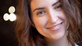 Close-upspruit van jong verleidelijk Kaukasisch wijfje die met charme glimlachen terwijl recht het bekijken camera met bokeh royalty-vrije stock afbeeldingen