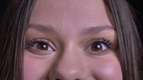 Close-upspruit van jong vrij Kaukasisch donkerbruin vrouwelijk gezicht met bruine ogen die recht camera met opwinding bekijken stock video