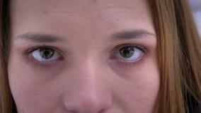 Close-upspruit van jong vrij Kaukasisch vrouwelijk gezicht met bruine ogen die camera in overpeinzing bekijken stock footage