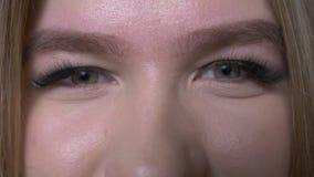 Close-upspruit van jong vrij Kaukasisch vrouwelijk gezicht met leuke ogen die die camera met achtergrond bekijken op zwarte wordt stock footage