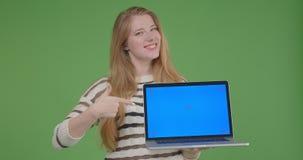 Close-upspruit van jong vrij Kaukasisch wijfje die laptop houden en het blauwe scherm tonen aan camera die cheerfully glimlachen stock video