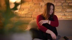 Close-upspruit van jong vrij Kaukasisch wijfje die op een show op TV met aandachtige gelaatsuitdrukking letten stock footage
