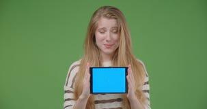 Close-upspruit van jong vrij Kaukasisch wijfje gebruikend de tablet en tonend het blauwe scherm aan camera die cheerfully glimlac stock footage