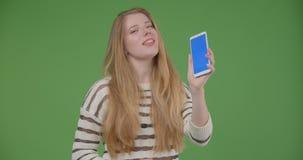 Close-upspruit van jong vrij Kaukasisch wijfje gebruikend de telefoon en tonend het blauwe scherm aan camera stock videobeelden