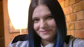 Close-upspruit van jong vrij Kaukasisch wijfje met geverft camera bekijken en haar die zijnd bij comfortabel huis binnen glimlach stock videobeelden