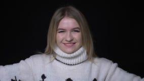 Close-upspruit van jong vrij Kaukasisch wijfje in sweater die en glimlachend gelukkig het bekijken camera met worden opgewekt stock videobeelden