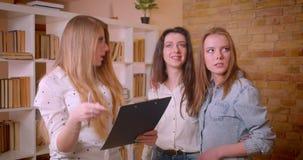 Close-upspruit van jong vrij lesbisch paar die een bespreking met vrouwelijke makelaar in onroerend goed over aankoop van een fla stock video