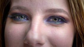 Close-upspruit van jong vrij vrouwelijk gezicht met ogen die camera bekijken die gelukkig met het overweldigen make-up glimlachen stock video