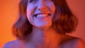 Close-upspruit van jong vrolijk Kaukasisch meisje met mooie make-up die cheerfully en camera met neon bekijken lachen stock video
