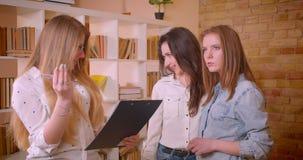 Close-upspruit van jong vrolijk lesbisch paar die aan vrouwelijke makelaar in onroerend goed over aankoop van een flat spreken stock footage