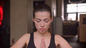 Close-upspruit van jonge aantrekkelijke atleet vrouwelijke het praktizeren yoga voor de camera in de gymnastiek binnen stock footage