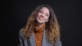 Close-upspruit van jonge aantrekkelijke Kaukasische cheerfully leunend hoofd glimlachen aan de kant en onderneemster die binnen s stock afbeeldingen