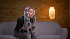 Close-upspruit van jonge aantrekkelijke Kaukasische hipster vrouwelijke het spelen videospelletjes op TV en het krijgen van geluk stock footage