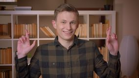 Close-upspruit van jonge aantrekkelijke Kaukasische mannelijke student die zijn gekruiste vingers hebben het zijn het hoopvolle b stock videobeelden