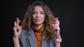 Close-upspruit van jonge aantrekkelijke Kaukasische onderneemster die haar vingers hebben die in bezorgdheid voor de camera worde stock foto