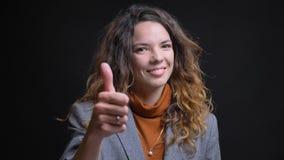 Close-upspruit van jonge aantrekkelijke Kaukasische onderneemster gesturing duim omhoog en cheerfully glimlachend met achtergrond stock foto