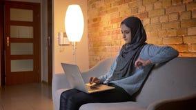Close-upspruit van jonge aantrekkelijke moslim vrouwelijke tiener in hijab gebruikend laptop en hebbend een videogesprek terwijl  stock video