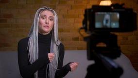 Close-upspruit van jonge aantrekkelijke vrouwelijke manier blogger met blonde dreadlocks het stromen het levende spreken op camer stock video