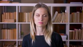 Close-upspruit van jonge aantrekkelijke vrouwelijke student die camera binnen in de universitaire bibliotheek bekijken stock footage