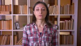 Close-upspruit van jonge aantrekkelijke vrouwelijke student die camera in de bibliotheek binnen bekijkt stock videobeelden