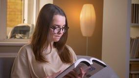 Close-upspruit van jonge aantrekkelijke vrouwelijke student die een boekzitting op de laag binnen in een comfortabele flat lezen stock videobeelden