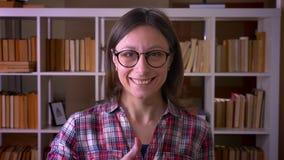 Close-upspruit van jonge aantrekkelijke vrouwelijke student in glazen die een duim tonen die omhoog camera in de bibliotheek binn stock video