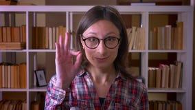 Close-upspruit van jonge aantrekkelijke vrouwelijke student in glazen die o.k. teken tonen die camera in de bibliotheek binnen be stock videobeelden