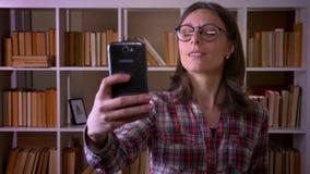 Close-upspruit van jonge aantrekkelijke vrouwelijke student in glazen die selfies en voor de camera in stellen nemen stock footage